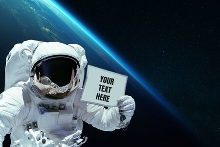 Spaceman in open space shows a card with your text here on the background of planet earth. Astronaut with advertising message