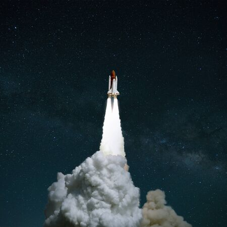 Successful take off of a spaceship against a starry sky. Rocket with smoke starts up. launch concept