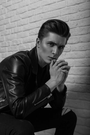 Studio portrait of a fashion young man with clean skin with a pierced nose with a trendy hairstyle in a stylish black leather jacket on a brick wall in the room. Sexy guy. Black and white photo.