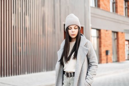 Pretty fashion young brunette woman in stylish knitted hat in vintage coat stands and looks down on the road near modern building on bright spring day. Model urban girl in trendy clothes. Casual look.