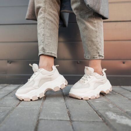 Modern young woman in stylish jeans in fashionable youth sneakers stands near wall in the city. Trendy women's shoes. Casual style. Closeup of female legs in fashion shoes.