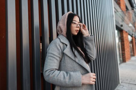 Modern urban stylish young woman model in fashionable long gray coat straightens stylish glasses near vintage metal wall in the city. Attractive trendy hipster girl poses outdoors. Street casual style Фото со стока