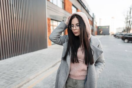 Attractive cute young hipster woman with black long hair in trendy pink hoodie in stylish gray coat in fashionable glasses poses and looking down near building in the city. Urban girl on the street.