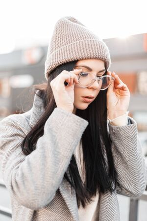 Young pretty attractive woman in stylish clothes puts on fashionable glasses on the background of bright sunlight in street.Portrait beautiful girl in casual trendy spring clothes in city in sunny day