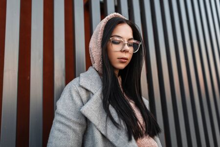 Fashion model young woman in spring stylish casual youth clothes in trendy glasses stands and looks down near metal gray building in the city. Portrait attractive trendy hipster girl outdoors. Style. Фото со стока