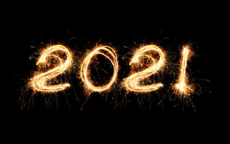 New Year 2021 text handmade written sparkles fireworks. Beautiful Shiny Golden numbers 2021 isolated on black background for design