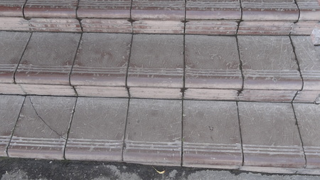 etch: Old maroon stone steps covered with graphite with scratches and cracks front view