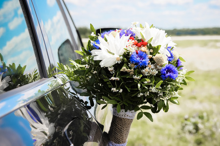 Wedding bouquet at the door of a black car Stock Photo