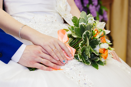 Detail of brides roses bouquet and hands holding Stock Photo