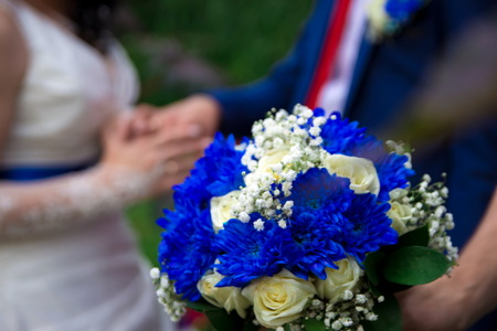 Hands and rings on the background of the costume of the groom and the bride's wedding bouquet 版權商用圖片
