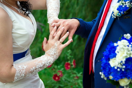 Hands and rings on the background of the costume of the groom and the brides wedding bouquet