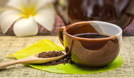Coffee lover.Coffee cup on green leaf with roasted coffee on wooden spoon.Background is a white plumeria and coffee pot. Stock Photo