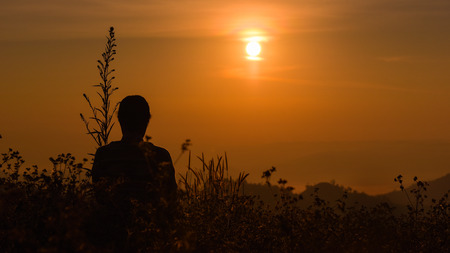 Back view of back light of a woman silhouette at warm sunrise in front of sun