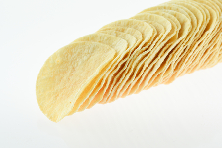 Multiple yellow potato chips snacks, composition isolated over the white background
