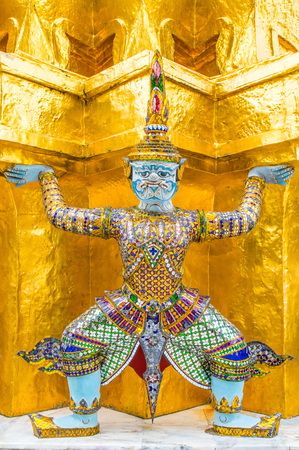 Demon Guardian/ Giant Statues stand around pagoda and hand to lift the base of the golden pagoda of thailand at wat phra kaew.