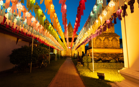 Gold pagoda and lantern hung up on the rail to the prosperity in loy kratong festival at wat phra that haripunchai lamphun Thailand during twilight. Archivio Fotografico
