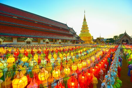CHIANG MAI THAILAND - OCTOBER 26, 2018 : Gold pagoda and lantern hung up on the rail to the prosperity in loy krathong festival at wat phra that hariphunchai lamphun Thailand during twilight.