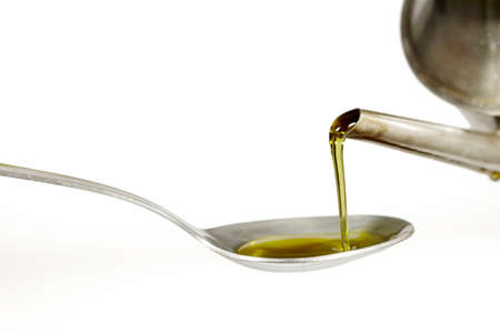 cruet: Filling up a tablespoon of extra virgin olive oil from a cruet