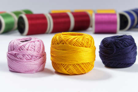 cotton thread: Skeins of cotton thread in foreground with bobbins for sewing machines in the background