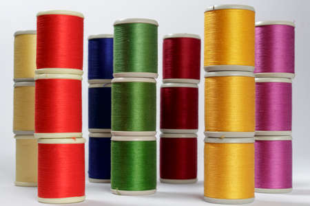 cotton thread: Several columns of bobbins of cotton thread for sewing machines with the colors of rainbow