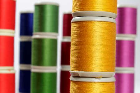 cotton thread: Close-up orange cotton thread bobbins. Other color threads in background
