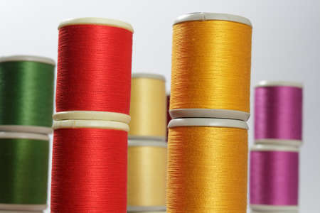 cotton thread: Close-up of cotton thread bobbins, orange and reds. Other color threads in background