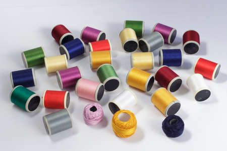 cotton thread: Several bobbins of cotton thread for sewing machines and thread skeins of different colors, on white background