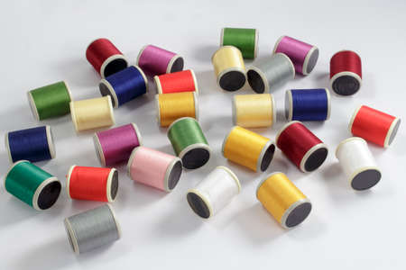 cotton thread: Diverse bobbins of cotton thread for sewing machines on white background