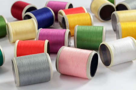 cotton thread: Close-up of bobbins of cotton thread for sewing machines; gray, pink and white threads in foreground Stock Photo