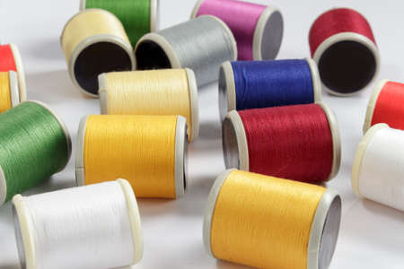 cotton thread: Several bobbins of cotton thread for sewing machines on white background Stock Photo