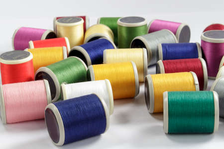 cotton thread: Close-up of bobbins of cotton thread for sewing machines; dark-blue and turquoise threads in foreground