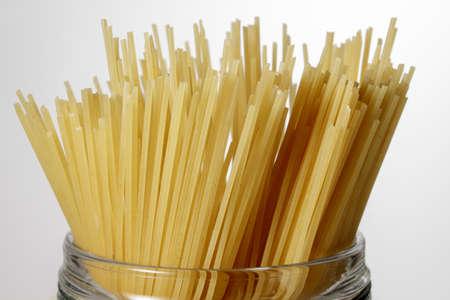 durum wheat semolina: Detail of Spaghetti in a glass jar on white background