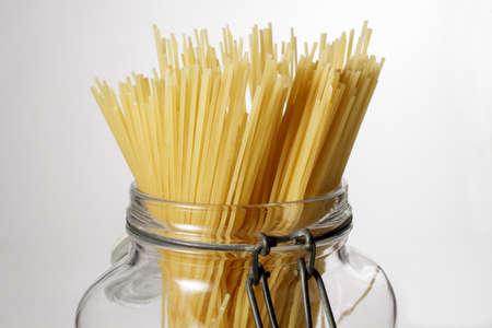 durum wheat semolina: Spaghetti in glass jar isolated on white background