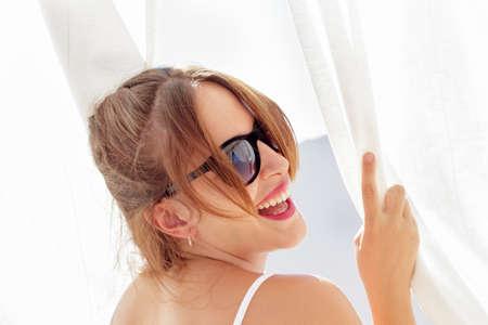 cortinas blancas: Mujer joven que r�e, con gafas de sol, mirar hacia atr�s mientras que agarra cortinas blancas vistos a contraluz