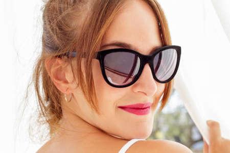 cortinas blancas: Primer plano de la sonrisa mujer joven con gafas de sol que mira hacia atr�s mientras que agarra cortinas blancas vistos a contraluz