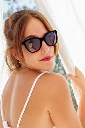 cortinas blancas: Vista vertical de la hermosa mujer con gafas de sol que mira hacia atr�s, entre las cortinas blancas