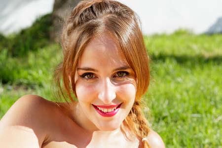 ojos verdes: Mujer bonita con los ojos verdes sonríe a la cámara mientras está acostado en la hierba