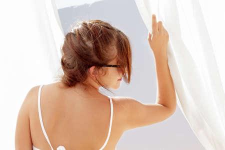 cortinas blancas: Mujer joven que presenta su espalda mientras que agarra cortinas blancas visto en retroiluminaci�n Foto de archivo