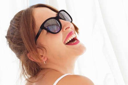 cortinas blancas: Primer plano de una hermosa mujer joven con gafas de sol que se est� riendo, entre cortinas blancas