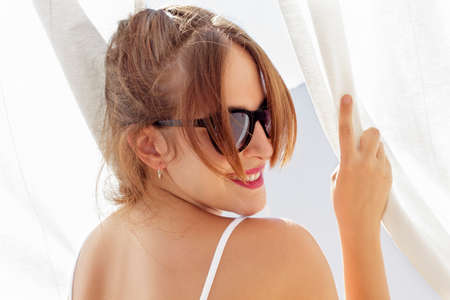 the backlighting: Smiling woman with sunglasses look back while clutching white curtains viewed at backlighting Stock Photo