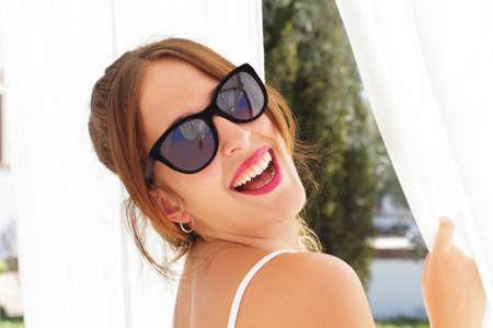 cortinas blancas: Joven y bella mujer con gafas de sol que se est� riendo, entre cortinas blancas