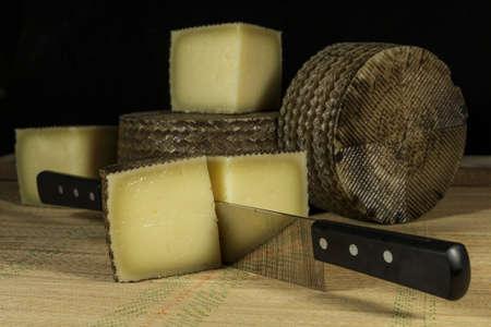 oveja: Queso de leche de oveja cutted en pedazos con un cuchillo de doble mango