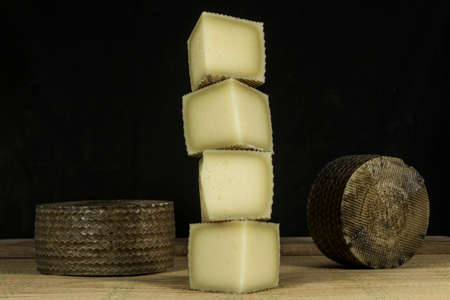 casein: Column of pieces of semi-hard cheese and two Manchego cheeses in background Foto de archivo