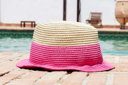 sun hat: Sun hat on the edge of a swimming pool Stock Photo