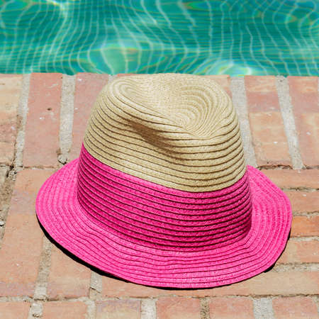 sun hat: Top view of sun hat on the edge of a swimming pool Stock Photo