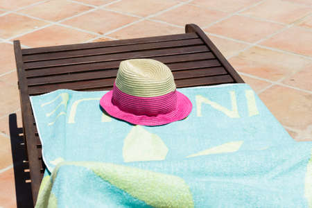 recliner: Sun hat and light blue towel on wooden sun recliner