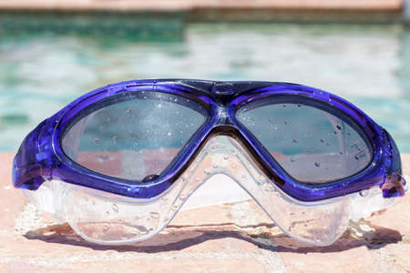 swim goggles: Frontal view of swim goggles on the edge of a swimming pool