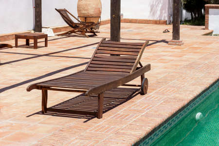 recliner: Wooden sun recliner beside a swimming pool Stock Photo