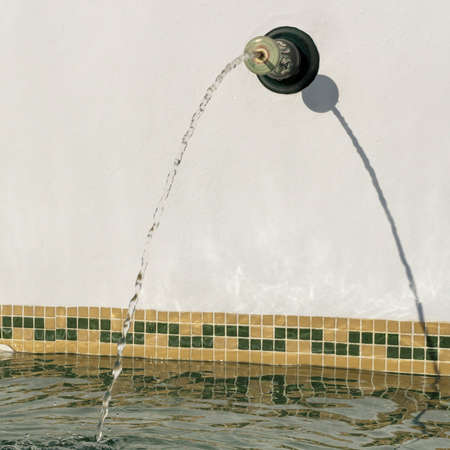 water jet: Water jet falling into a swimming pool Stock Photo