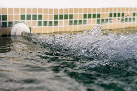 water jet: Lateral view of inflowing water jet into a pool Stock Photo
